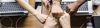 Five people fist bumping over their desks and lap tops