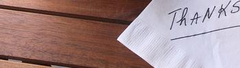 """A hand written note on white paper stating """"Thanks"""" on a desk next to a plant."""