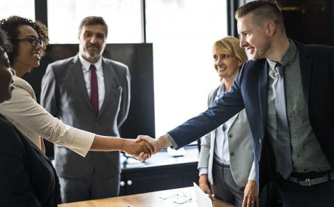 A diverse group of business people standing as a young white male reaches across the table and shakes hands with a young African American female.