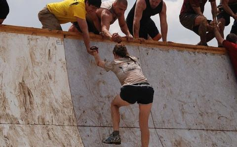 team helping a team member over a high wall