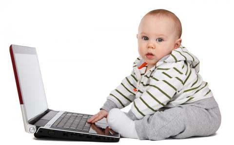 Baby touching a key board and looking back at us