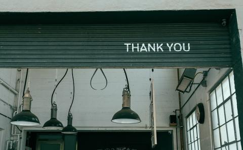 Thank you on a steel garage door security panel in a partially opened state with lamps hanging from the ceiling