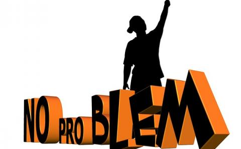 """Person with paint roller painting over the word """"Problem"""" and standing in front of the words """"No Problem"""""""