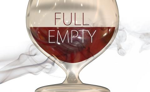 A glass of red wine half full with the upper of the glass half labeled full and the lower half labeled empty