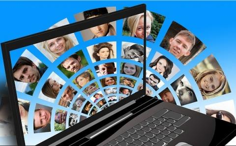 lap top computer with a host of international faces coming out of the screen