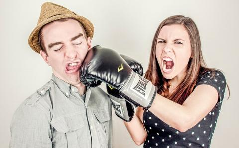 Woman with boxing glove hitting man in the face
