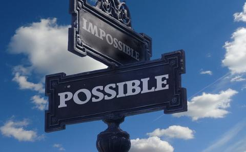 A street sign at the intersection of Impossible and Possible with a background blue sky with some white clouds