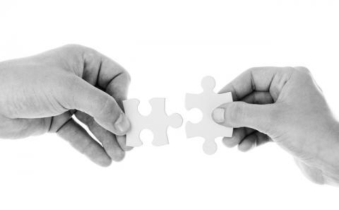 Two hands with two puzzle pieces pushing them together