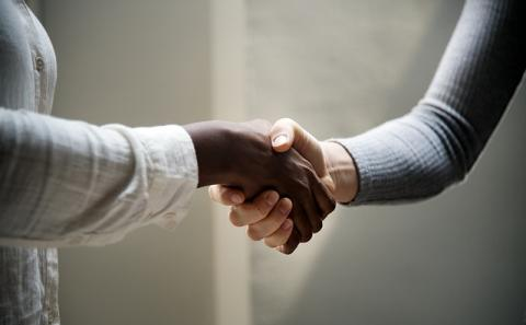One black hand and one white hand shaking hands.