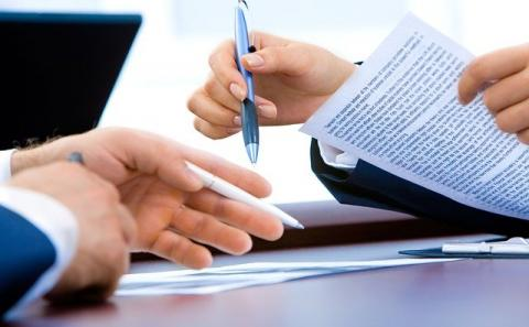 Only seeing the hands and a table with two people across from each other and one pointing a pen down while holding a paper with writing on it in the other hand