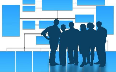 Organization chart in the background and silhouette's of a group of professionals in the foreground