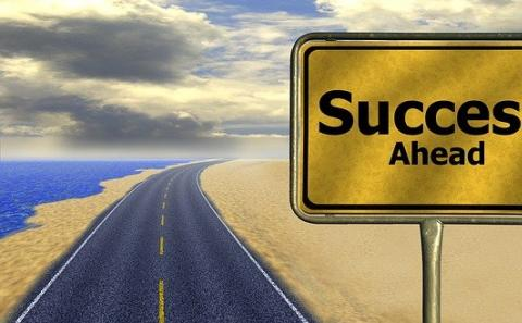 Two lane paved road with centerline leading to infinity with a sign to the right that reads Success Ahead.