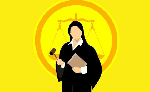 A judge in a robe with the balance of justice scales in the background