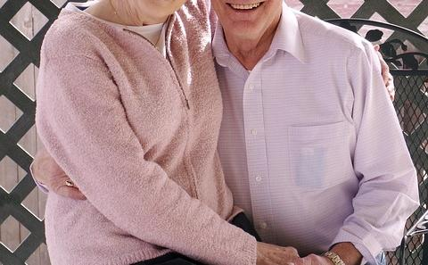 Older couple smiling with each other sitting on a bench