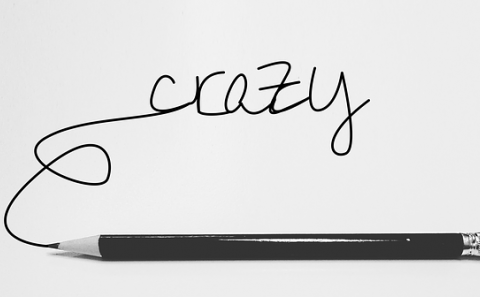 The word crazy in script hand writing written with a pencil and the pencil laying under the word