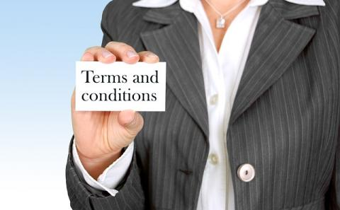 "A business person holding a card that states ""terms and conditions"""