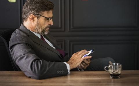Man in suit sitting at desk looking at phone and texting