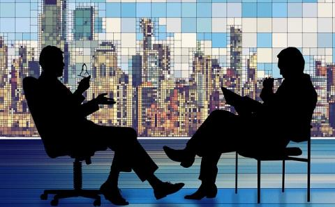 Two black silhouettes in deep discussion with a skyline in the background