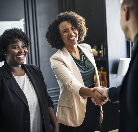 Two women with big smiles with one shaking hands with a man