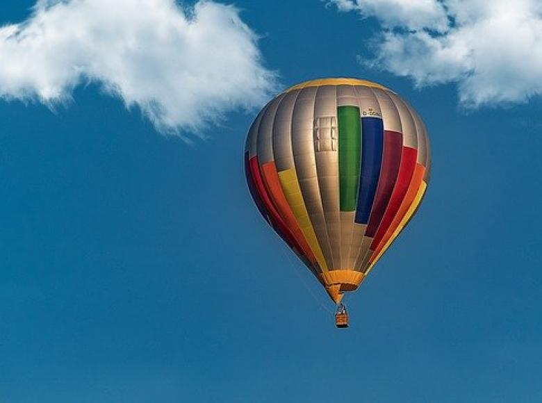Colorful air balloon in a blue sky with two clouds