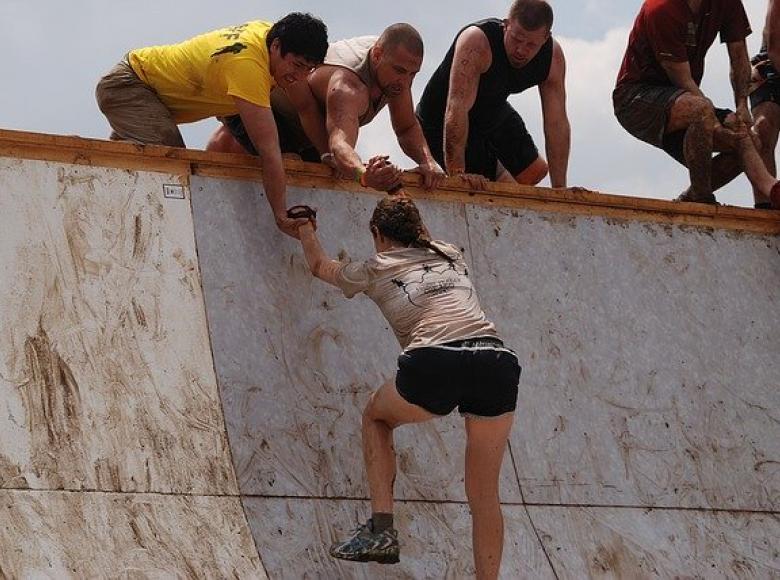 team helping a team member over a high wall