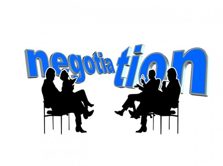 two black silhouettes on the left and the right with the word negotiation in blue behind them