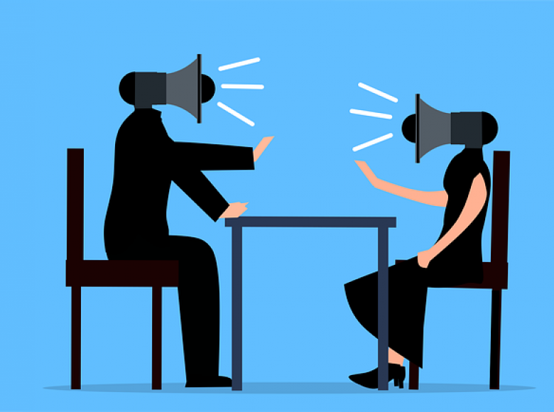 An image of man and a woman on opposite sides of a table and in place of heads they have megaphones yelling at each other