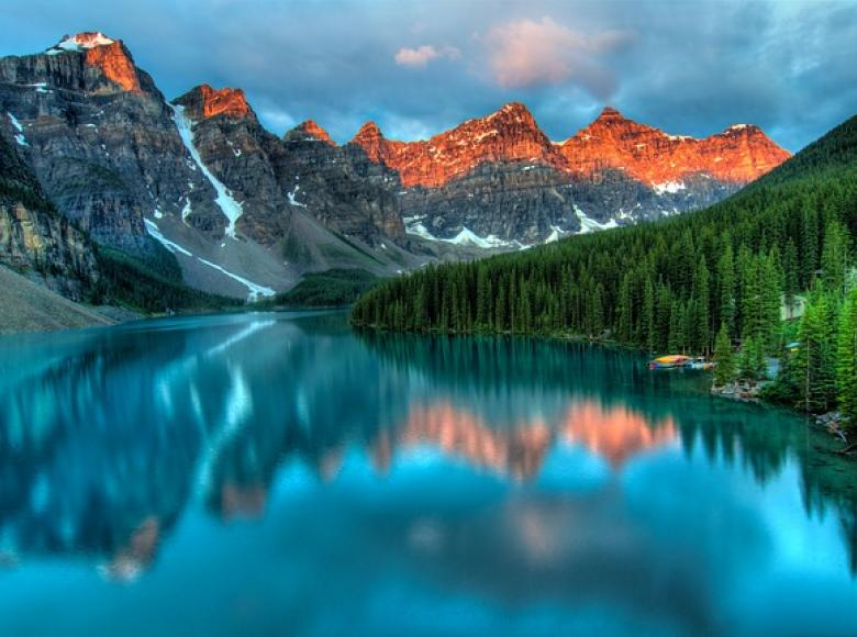 Beautiful sunset with mountains and reflection off of a mountain lake