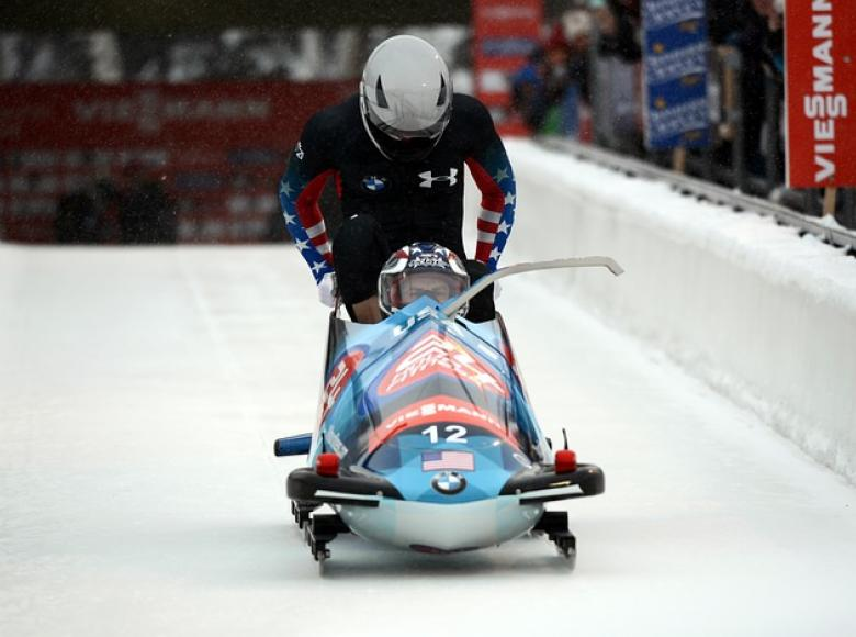 A two man bobsled taking off out of the starting gate