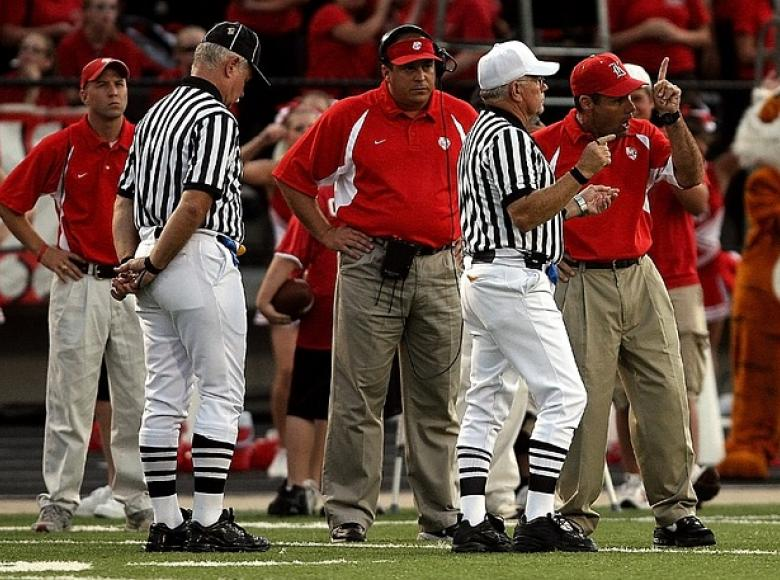 Two referees and three coaches body language interaction at a football game