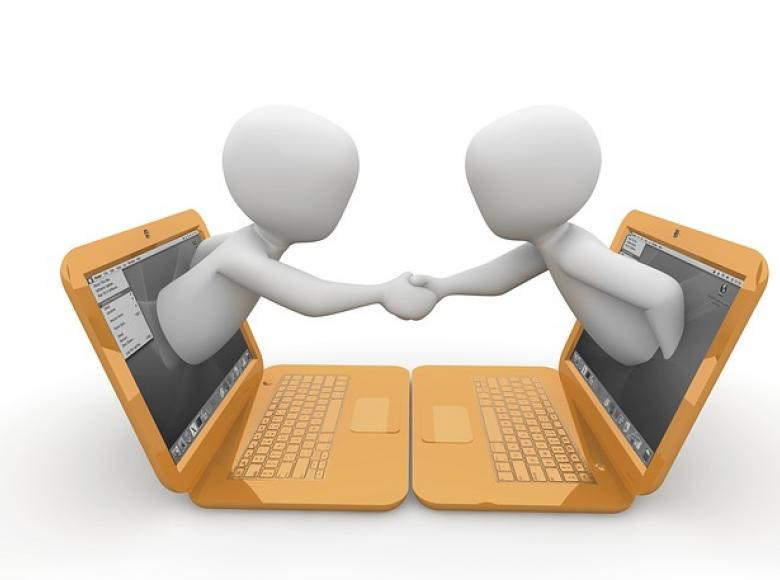 Two characters facing each other coming out of their computer screens and shaking hands