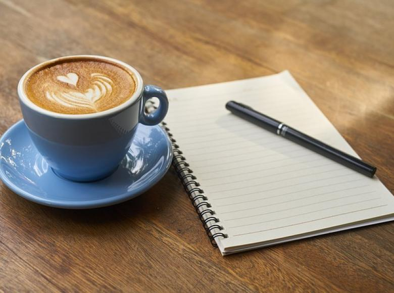 A cup of coffee with a notepad and pencil
