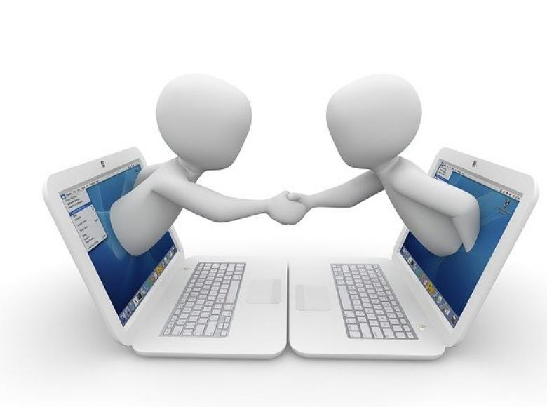 Two computer laptops facing each other with individuals coming out of their screens to shake hands with one another