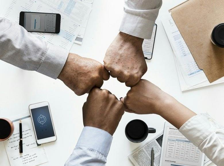 four fist bumps over a table with coffee, smart phones and papers. The four fist bumps represent men, women, and people of color