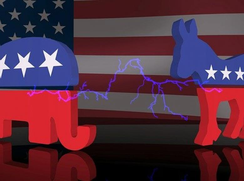 Red white and blue republican elephant and democratic donkey on stage in front of an American flag with an electric shock between the two