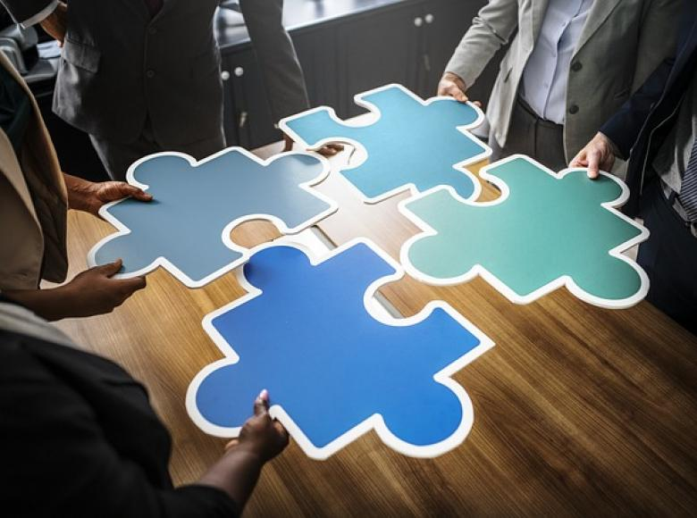 Four big puzzle pieces coming together on a table held by 4 individuals