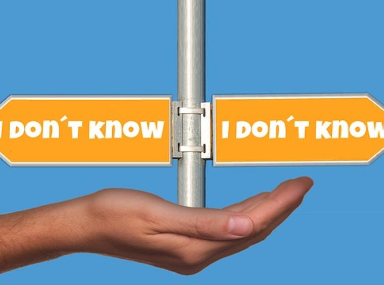 "A hand holding up a pole. On the pole are signs pointing each direction that state ""I don't know"""