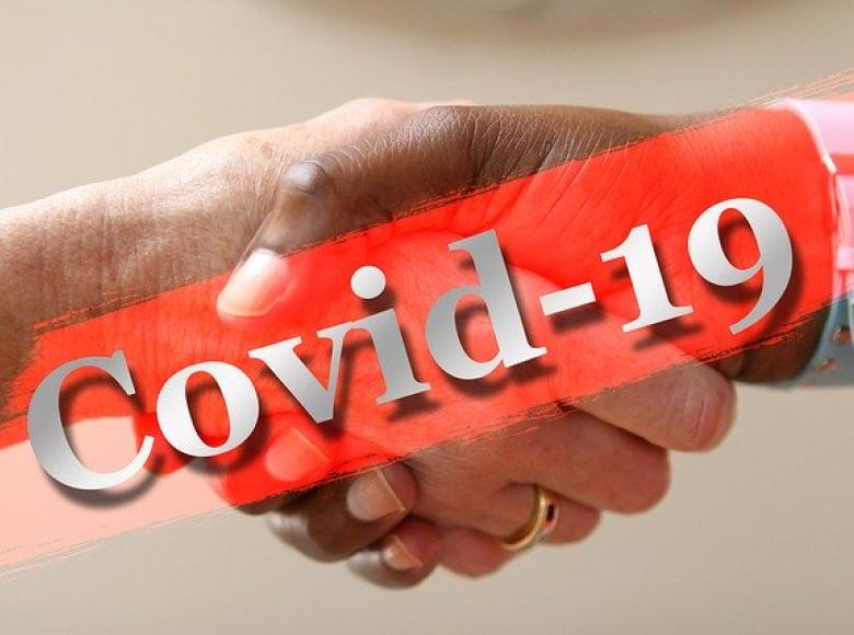 Covid-19 in white letters with red background in front of two shaking hands