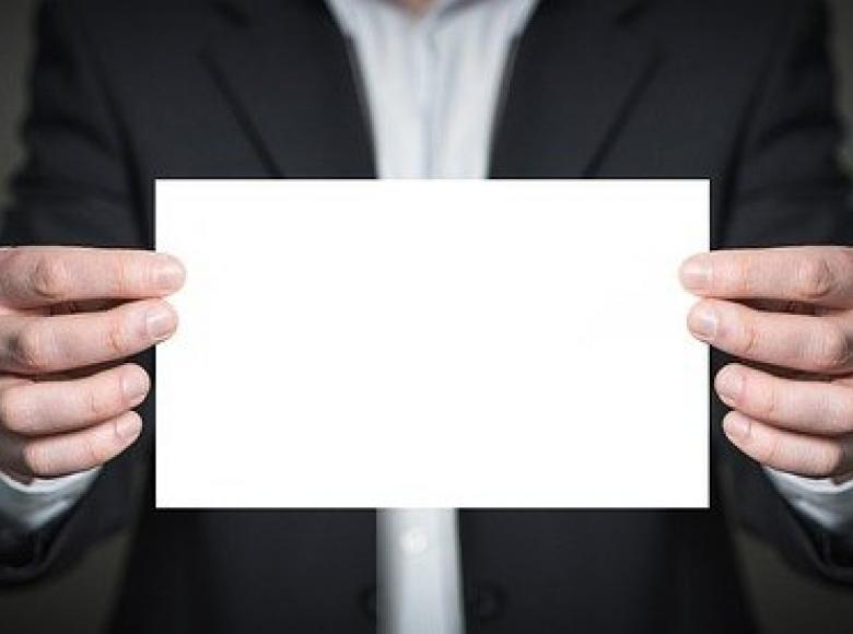 Man holding up a blank card