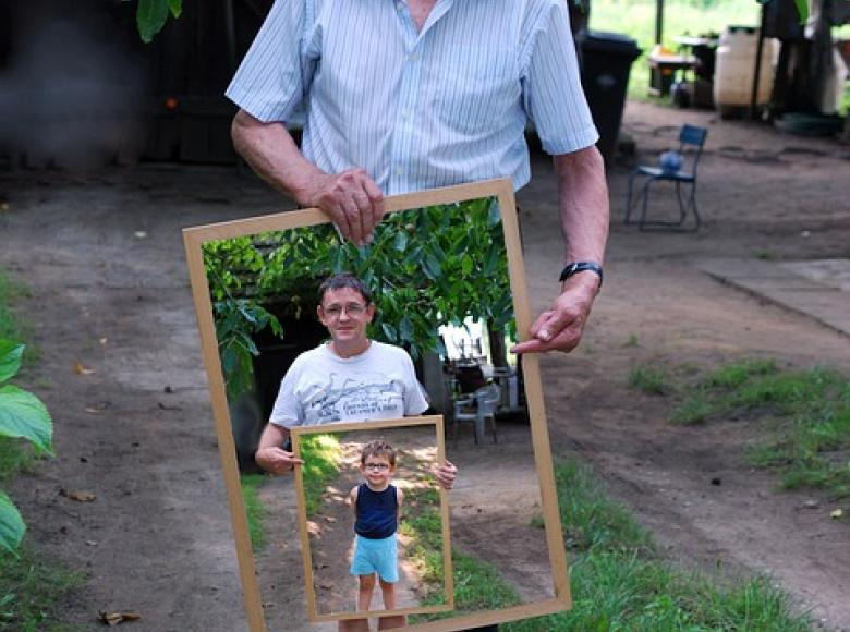 Older gentleman holding a picture of himself, son, and granchilc
