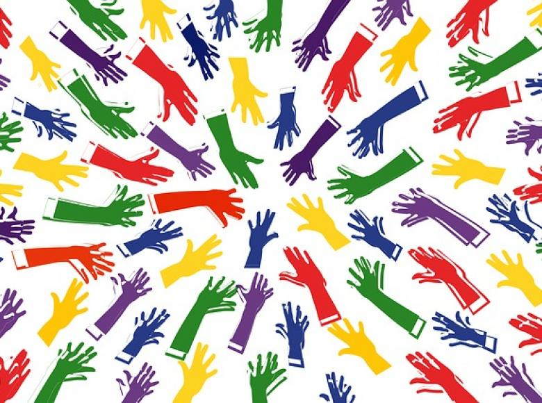 Multiple colored hands from all directions pointing towards the center