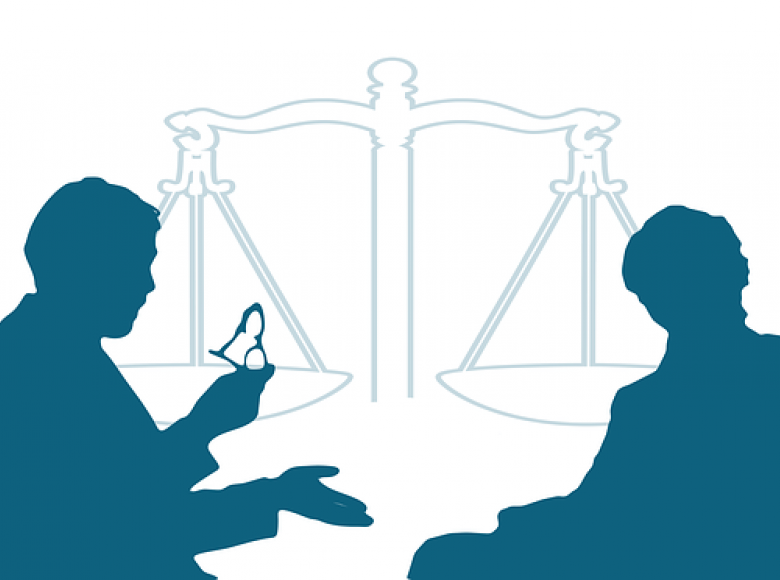 Silhouettes of a man with glasses and woman conversing with each other and the scales of justice in the background