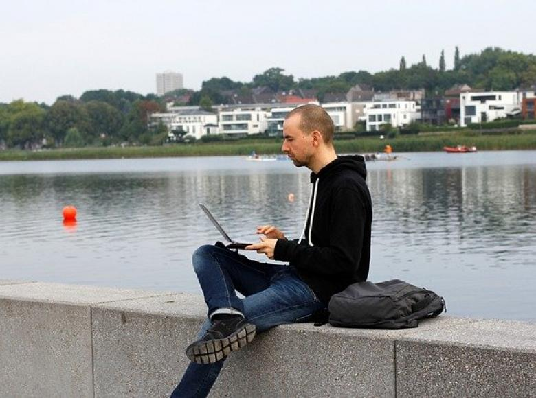 Person sitting next to a river working on their laptop