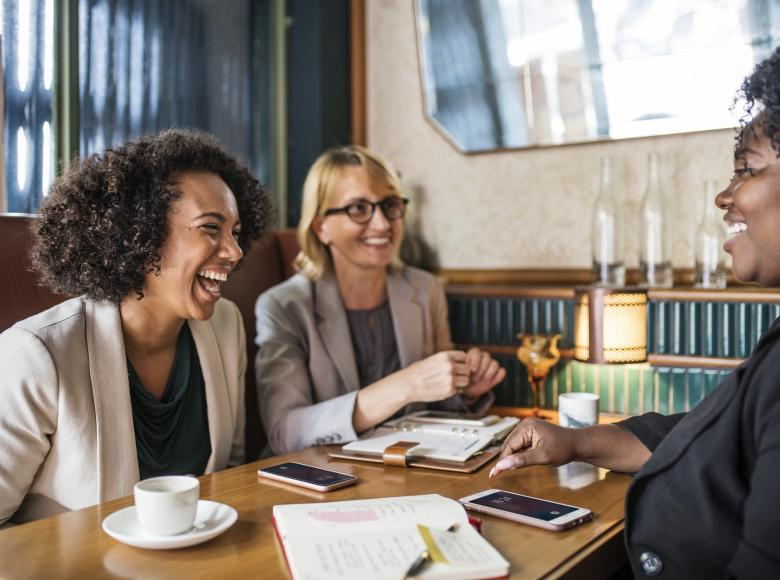 Three adult women having coffee while having a pleasant conversation in a coffee shop booth