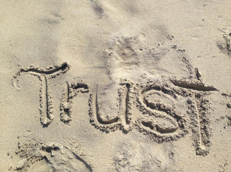 The word Trust scratched into a sandy beach