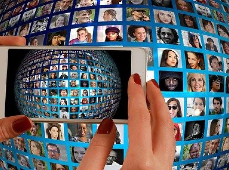 A large ball with many faces on the ball being photographed by a smart phone